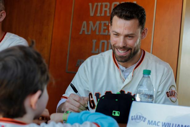 Mac Williamson (51) signs a young fans hat during the Giants Fan Fest at AT&T Park on Feb. 11, 2017.