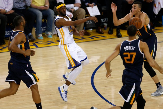 Golden State Warriors guard Ian Clark (21) dishes through the Jazz defenders in the first half as the Utah Jazz face the Golden State Warriors at Oracle Arena in Oakland, Calif., on Monday, April 10, 2017.