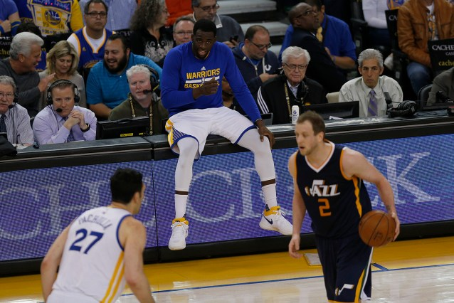 Golden State Warriors forward Draymond Green (23) watches the game from the scorers table before he enters the game in the first half as the Utah Jazz face the Golden State Warriors at Oracle Arena in Oakland, Calif., on Monday, April 10, 2017.