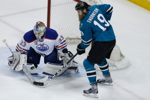 A puck off the stick of San Jose Sharks Logan Couture finds its way past Edmonton Oilers goaltender Cam Talbot as Joe Thorton looks on during San Jose's 7-0 win over Edmonton in Game 2 of their playoff series Tuesday night at SAP Center.