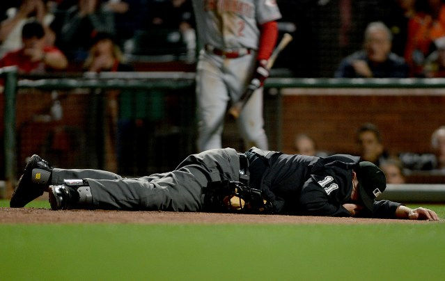 Umpire Tony Randazzo (11) lays on the ground after hit by an errant throw as the Cincinnati Reds face the San Francisco Giants at AT&T Park in San Francisco, Calif., on Friday, May 12, 2017.