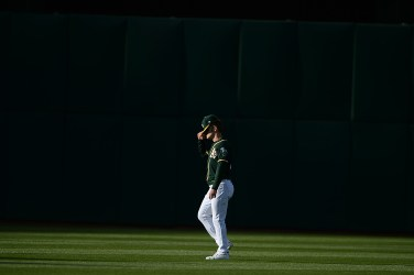 Oakland Athletics left fielder Mark Canha (20) adjusts his cap before the Toronto Blue Jays face the Oakland Athletics at Oakland Coliseum in Oakland, Calif., on Tuesday, June 6, 2017.