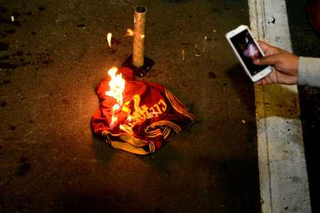 A Golden State Warriors fan records a video on his cell phone of a Cleveland Cavaliers star LeBron James jersey on fire after the Warriors beat the Cavaliers to win the NBA Finals in Oakland, Calif. on Monday, Jun. 12, 2017.