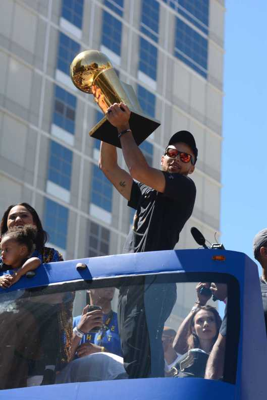 Warriors G Stephen Curry (30) hoists the NBA Championship trophy at the Golden State Warriors championship parade in Oakland, Calif. on Thursday, Jun. 15, 2017.