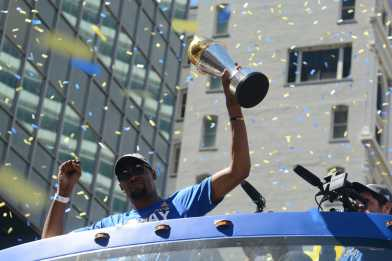 Warriors forward Kevin Durant raises his MVP trophy at the Golden State Warriors championship parade in Oakland Thursday.