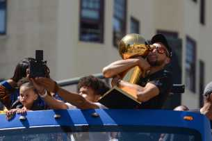 Warriors G Stephen Curry (30) hugs the 2017 NBA Championship trophy at the Golden State Warriors championship parade in Oakland, Calif. on Thursday, Jun. 15, 2017.