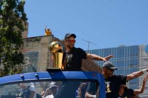 Warriors G Stephen Curry (30) holds the 2017 NBA Championship trophy and waves to the crowd at the Golden State Warriors championship parade in Oakland, Calif. on Thursday, Jun. 15, 2017.