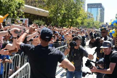 Warriors G Stephen Curry (30) high-fives Warriors fans at the Golden State Warriors championship parade in Oakland, Calif. on Thursday, Jun. 15, 2017.