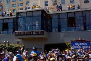 Fans and onlookers at the Lake Merritt Hotel peers out the window at the Golden State Warriors championship parade in Oakland, Calif. on Thursday, Jun. 15, 2017.