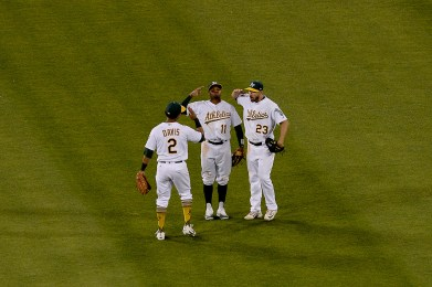 Oakland Athletics left fielder Khris Davis (2), center fielder Rajai Davis (11), and right fielder Matt Joyce (23) celebrate a 7-6 victory over the New York Yankees at Oakland Coliseum in Oakland, Calif., on Friday, June 16, 2017.