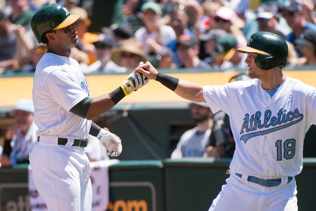Oakland Athletics left fielder Khris Davis (2) celebrates with shortstop Chad Pinder (18) after hitting a two-run home run in the third inning of the game against the New York Yankees at the Oakland Coliseum in Oakland, Calif., on June 18, 2017.