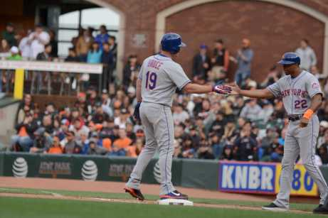 New York Mets outfielder Jay Bruce (19) high-fives Mets first base coach Tom Goodwin (21) after singling in a run in the eight inning to give the Mets a 2-1 lead as the New York Mets face the San Francisco Giants at AT&T Park in San Francisco, Calif., on Friday, June 24, 2017.
