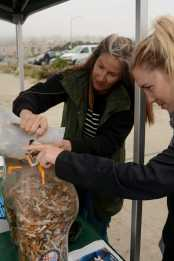Michele McEntee (left), 54, a volunteer for the organization Surfriders from San Francisco, pours cigarette butts she collected into a butt-shaped receptacle at Ocean Beach in San Francisco, Calif., on Friday, June 30, 2017. SF Supervisors Katy Tang and Sandra Lee Fewer helped launch a pilot program to encourage people to throw their cigarettes away in receptacles instead of throwing them away on the streets.