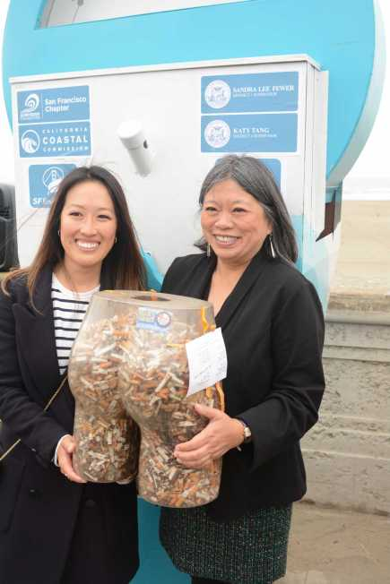 SF Supervisors Katy Tang (left) and Sandra Lee Fewer (right) hold a butt-shaped receptacle filled with cigarette butts while posing for a photograph at Ocean Beach in San Francisco, Calif., on Friday, June 30, 2017. Tang and Fewer helped launch a pilot program to encourage people to throw their cigarettes away in receptacles instead of throwing them away on the streets.