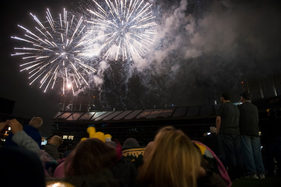 Fans relax on the field and enjoy the fireworks show following the game between the Oakland Athletics and the Chicago White Sox at the Oakland Coliseum in Oakland, Calif., on July 3, 2017.
