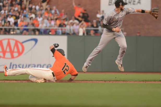 San Francisco Giants second baseman Joe Panik (12) slides under the tag of Miami Marlins second baseman Dee Gordon (9) in the first inning as the Miami Marlins face the San Francisco Giants at AT&T Park on Friday, July 7, 2017.