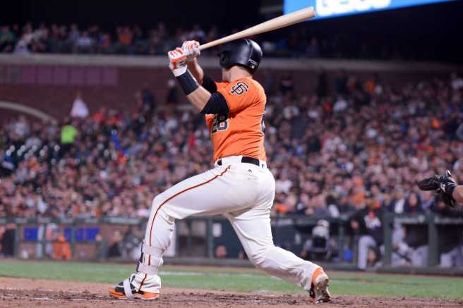 San Francisco Giants catcher Buster Posey (28) hits a bloop single in the eighth inning as the Miami Marlins face the San Francisco Giants at AT&T Park on Friday, July 7, 2017.