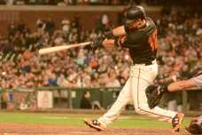 San Francisco Giants second baseman Joe Panik (12) singles to center in the ninth inning, scoring Giants shortstop Brandon Crawford (35) from third base, as the Miami Marlins face the San Francisco Giants at AT&T Park on Friday, July 8, 2017.