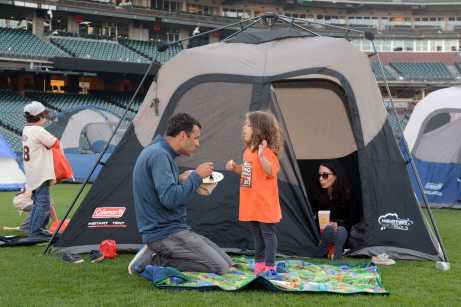 Anousheh Khaghani (center), 3, talks to her parents Brian Lutz (left), 40, a lawyer from San Francisco, Calif., and Leah Khaghani (right), a psychologist from San Francisco, at the Giants slumber party after the Miami Marlins beat the San Francisco Giants at AT&T Park on Friday, July 9, 2017.