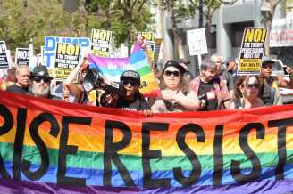 Alex Morrison (center with megaphone), a drag king and producer from Berkeley, Calif. who was a grand marshal in the 2017 LGBTQ Pride parade, marches and chants at an anti-Trump protest in San Francisco, Calif., on Saturday, July 15, 2017.