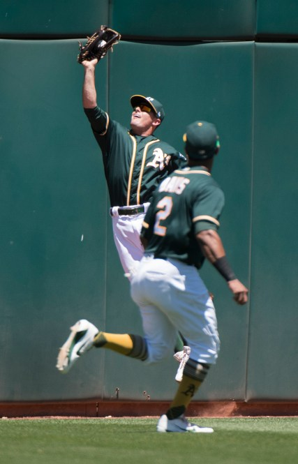 Oakland Athletics center fielder Jaycob Brugman (38) makes a leaping catch in the third inning of the game against the Cleveland Indians at the Oakland Coliseum in Oakland, Calif., on July 16, 2017.