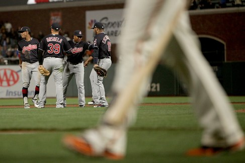 Cleveland Indians celebrate a 5-3 victory as San Francisco Giants catcher Buster Posey (28) walks off the field after recording the last out at AT&T Park in San Francisco, Calif., on Monday, July 17, 2017.