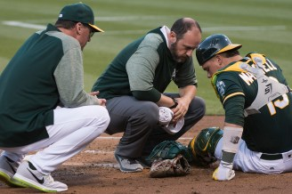 Oakland Athletics Manager Bob Melvin (6) and Head Trainer Nick Paparesta check on catcher Bruce Maxwell (13) after Maxwell took a foul ball off his facemask in the second inning of the game against the Tampa Bay Rays at the Oakland Coliseum in Oakland, Calif., on July 17, 2017.