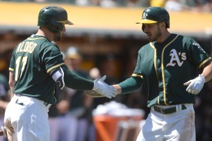 Oakland Athletics right fielder Matt Joyce (23) is congratulated by Oakland Athletics first baseman Yonder Alonso (17) after hitting a home run in the eighth inning as the Tampa Bay Rays face the Oakland Athletics at Oakland Coliseum in Oakland, Calif., on Wednesday, July 19, 2017.