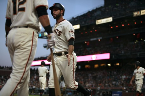 San Francisco Giants first baseman Brandon Belt (9) is congratulated after scoring in the fourth inning as the Pittsburgh Pirates face the San Francisco Giants at AT&T Park in San Francisco, Calif., on Monday, July 24, 2017.