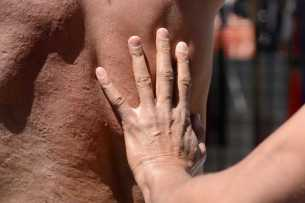 A man identified as Karl puts his hand on River Strongman (right), 23, a kink, HIV, sex-positive and mental health activist from Los Angeles, Calif, after flogging him at the Up Your Alley fair in the South of Market district of San Francisco, Calif., on Sunday, July 30, 2017.