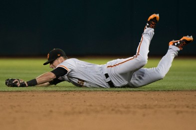San Francisco Giants second baseman Joe Panik (12) makes a sliding save on the ball in the fourth inning of the game against the Oakland Athletics at the Oakland Coliseum in Oakland, Calif., on July 31, 2017.