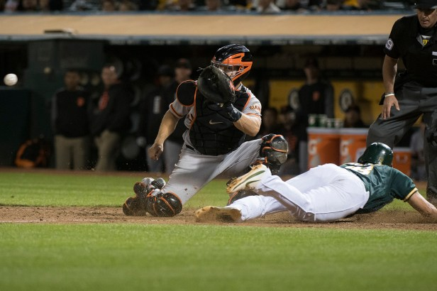 Oakland Athletics pinch runner Chad Pinder (18) slides safely into home as San Francisco Giants catcher Nick Hundley (5) waits for a late throw in the eighth inning of the game at the Oakland Coliseum in Oakland, Calif., on July 31, 2017.