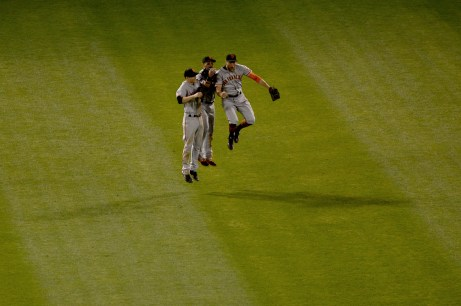 San Francisco Giants left fielder Kelby Tomlinson (37), center fielder Gorkys Hernandez (66) and right fielder Hunter Pence (8) celebrate a 10-4 victory over the Oakland Athletics at Oakland Coliseum in Oakland, Calif., on Tuesday, August 1, 2017.