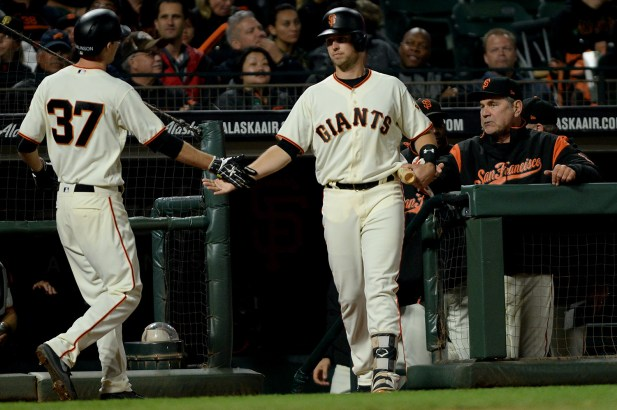 San Francisco Giants second baseman Kelby Tomlinson (37) is congratulated by first baseman Buster Posey (28) after scoring in the seventh inning as the Chicago Cubs face the San Francisco Giants at AT&T Park in San Francisco, Calif., on Tuesday, August 8, 2017.
