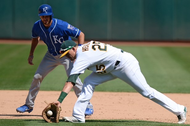 Oakland Athletics designated hitter Ryon Healy (25) snags a roundball hit by Kansas City Royals second baseman Whit Merrfield (15) in the eighth inning as the Kansas City Royals face the Oakland Athletics at Oakland Coliseum in Oakland, Calif., on Wednesday, August 16, 2017.