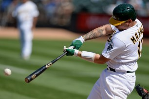 Oakland Athletics catcher Bruce Maxwell (13) singles in the eighth inning as the Kansas City Royals face the Oakland Athletics at Oakland Coliseum in Oakland, Calif., on Wednesday, August 16, 2017.