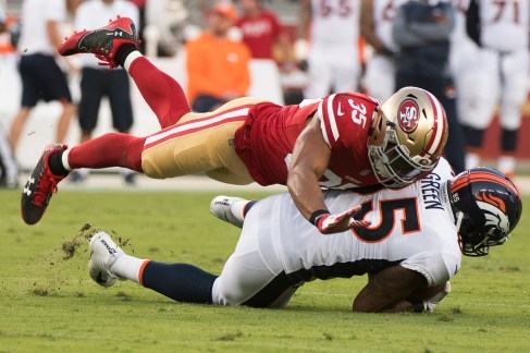 San Francisco 49ers safety Eric Reid (35) tackles Denver Broncos tight end Virgil Green (85) in the first quarter of the game at Levi's Stadium in Santa Clara, Calif., on August 19, 2017.