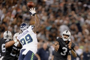 Oakland Raiders quarterback EJ Manuel (3) launches a touchdown pass in the second quarter as the Seattle Seahawks face the Oakland Raiders at Oakland Coliseum in Oakland, Calif., on Thursday, August 31, 2017.