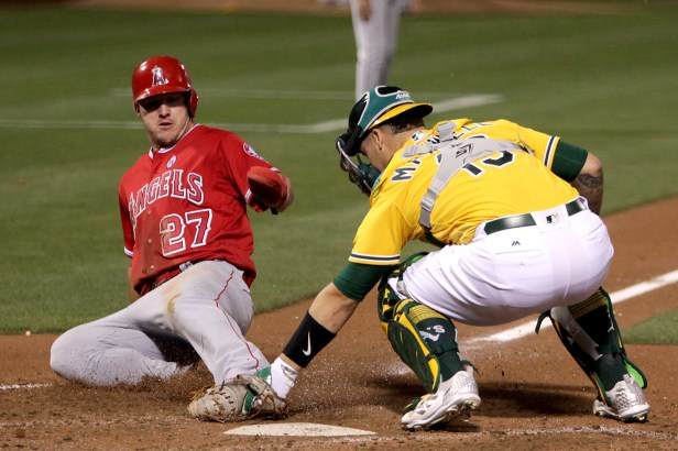 Los Angeles Angels center fielder Mike Trout (27) is tagged out by Oakland Athletics catcher Bruce Maxwell (13) in the third inning as the Los Angeles Angels face the Oakland Athletics at Oakland Coliseum in Oakland, Calif., on Saturday, April 1, 2017.