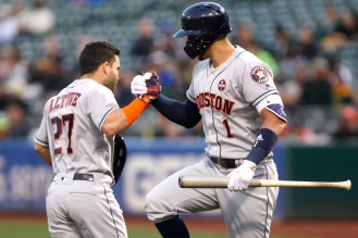 Houston Astros second baseman Jose Altuve (27) celebrates with Houston Astros shortstop Carlos Correa (1) after hitting a home run during the first inning as the Houston Astros face the Oakland Athletics at the Oakland Coliseum on Friday September 08, 2017.