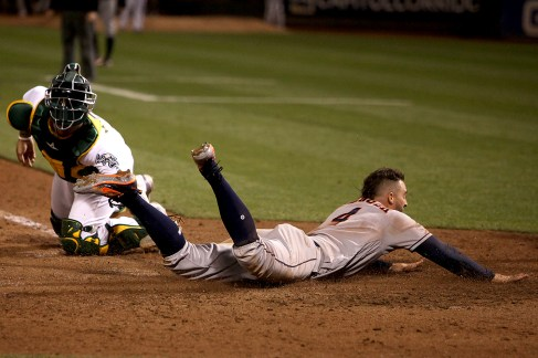 Houston Astros right fielder George Springer (4) scores in the ninth inning as the Houston Astros face the Oakland Athletics at Oakland Coliseum in Oakland, Calif., on Friday, September 8, 2017.
