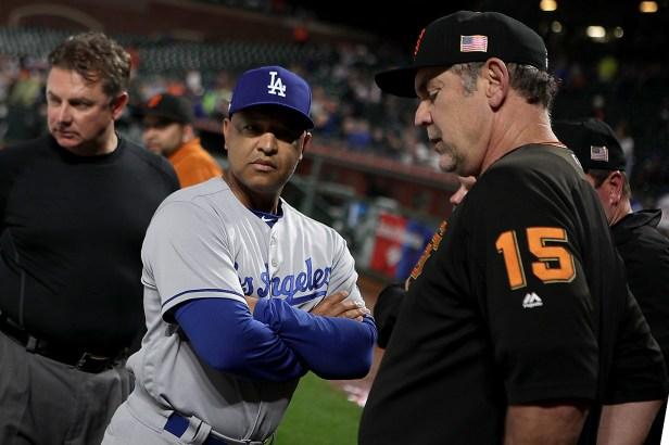 Los Angeles Dodgers manager Dave Roberts (30), San Francisco Giants manager Bruce Bochy (15) and the officiating crew talk during a rain delay as the Los Angeles Dodgers face the San Francisco Giants at AT&T Park in San Francisco, Calif., on Monday, September 11, 2017.