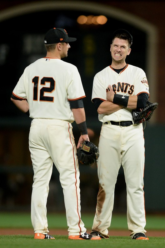 San Francisco Giants second baseman Joe Panik (12) and first baseman Buster Posey (28) talk during a pitching change in the seventh inning as the Los Angeles Dodgers face the San Francisco Giants at AT&T Park in San Francisco, Calif., on Monday, September 11, 2017.
