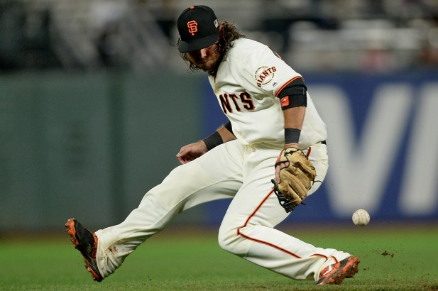 San Francisco Giants shortstop Brandon Crawford (35) can't handle a Los Angeles Dodgers infielder Logan Forsythe (11) infield hit as the Los Angeles Dodgers face the San Francisco Giants at AT&T Park in San Francisco, Calif., on Monday, September 11, 2017.