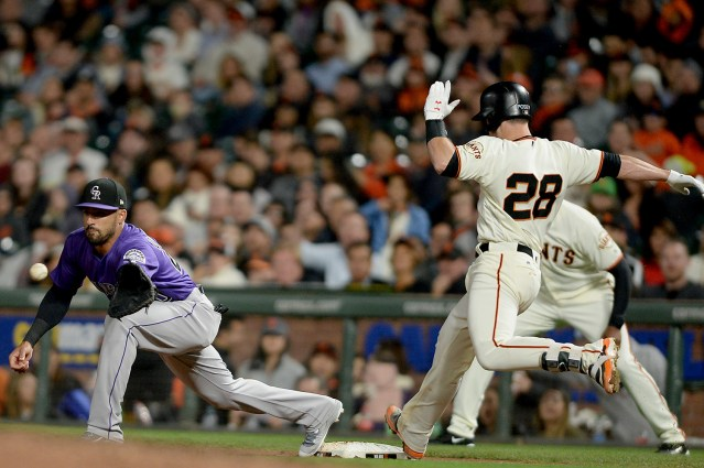San Francisco Giants catcher Buster Posey (28) beats the throw for a single in the fourth inning as the Colorado Rockies face the San Francisco Giants at AT&T Park in San Francisco, Calif., on Tuesday, September 19, 2017.