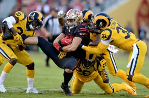 San Francisco 49ers' George Kittle (85) is brought down by the defense in the first half as the Los Angeles Rams face the San Francisco 49ers at Levi's Stadium in Santa Clara, Calif., on Thursday, September 21, 2017.