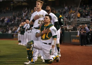 Oakland Athletics catcher Bruce Maxwell (13) kneels during the National Anthem as Oakland Athletics left fielder Mark Canha (20) places his hand on Maxwell's shoulder before the Seattle Mariners face the Oakland Athletics at Oakland Coliseum in Oakland, Calif., on Monday, September 25, 2017.