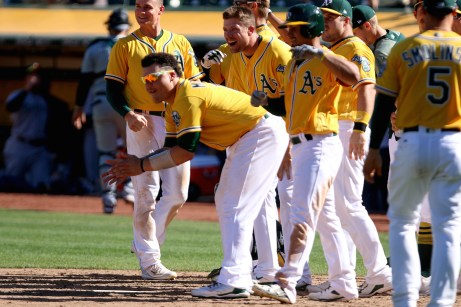 Oakland Athletics catcher Bruce Maxwell (13) and other teammates wait to greet Oakland Athletics left fielder Mark Canha (20) after hitting a home run to win their game against the Seattle Mariners at the Oakland Coliseum on Wednesday, September 27, 2017. Athletics won 6-5.