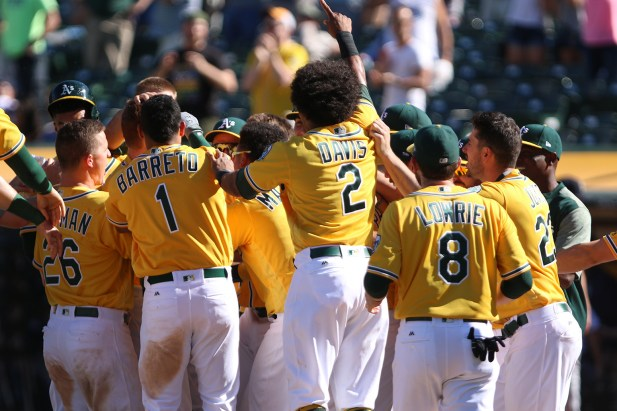 Oakland Athletics players celebrate after left fielder Mark Canha (20) makes it across home plate after hitting a home run to win their game against the Seattle Mariners at the Oakland Coliseum on Wednesday, September 27, 2017. Athletics won 6-5.