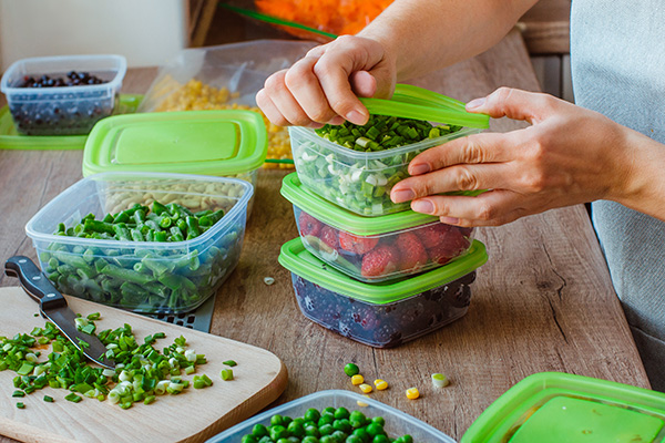 Woman putting fruits, vegetables into plastic containers